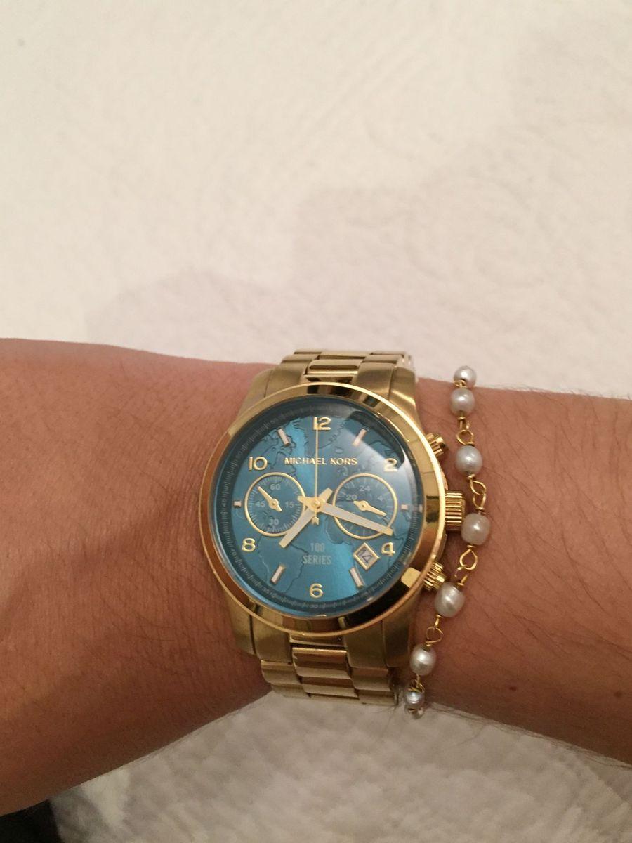 de89d5e0c06 relogio michael kors dourado com fundo azul turquesa - relógios michael kors